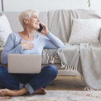 Cheerful elderly business woman talking by phone with clients from home, sitting on floor and using laptop, free space