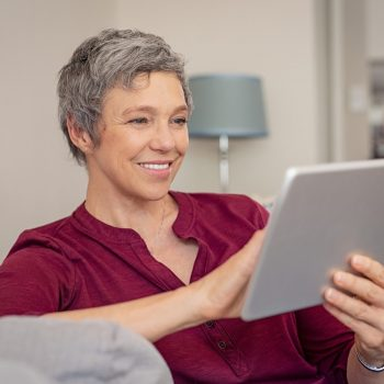 Smiling senior woman looking her digital tablet while sitting on